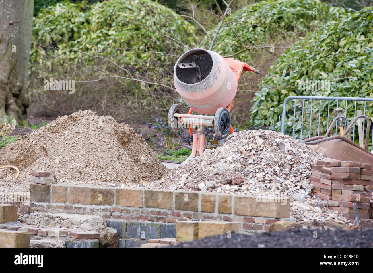 A cement concrete mixer and building materials on site whilst carrying out a hard landscaping job - Stock Image