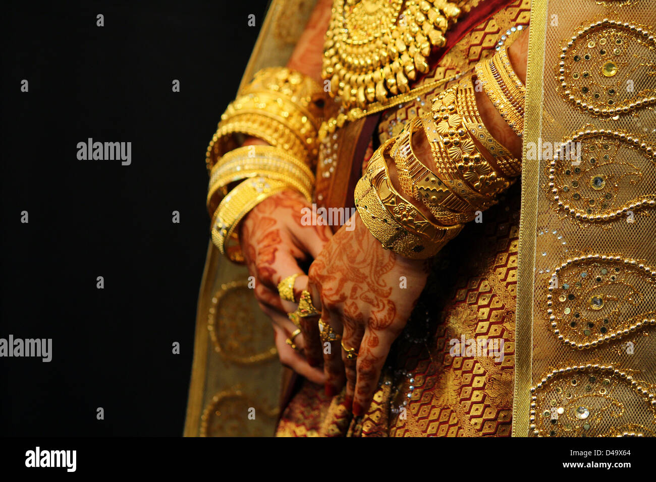 rich gold jewelery on the hands of a muslim bride in india - Stock Image