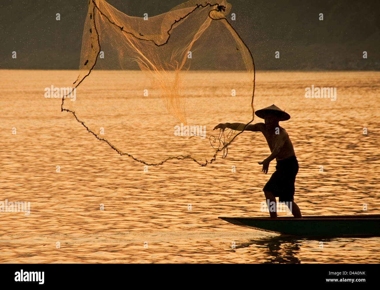 Fisherman tossing net on Mekong River at Luang Prabang, Laos - Stock Image