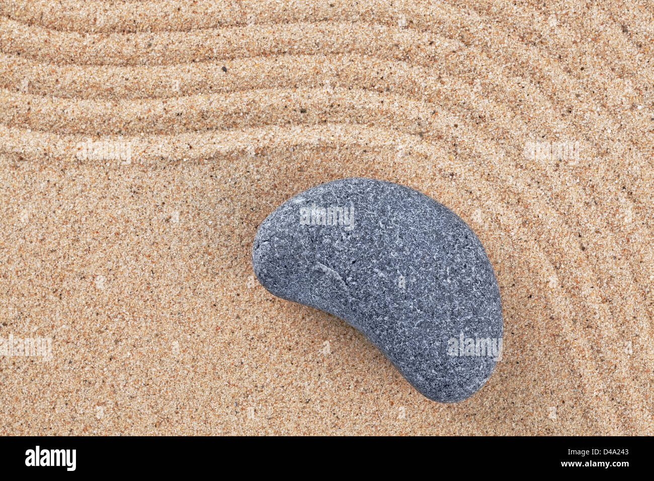 A curved pebble on a raked sand zen garden - Stock Image