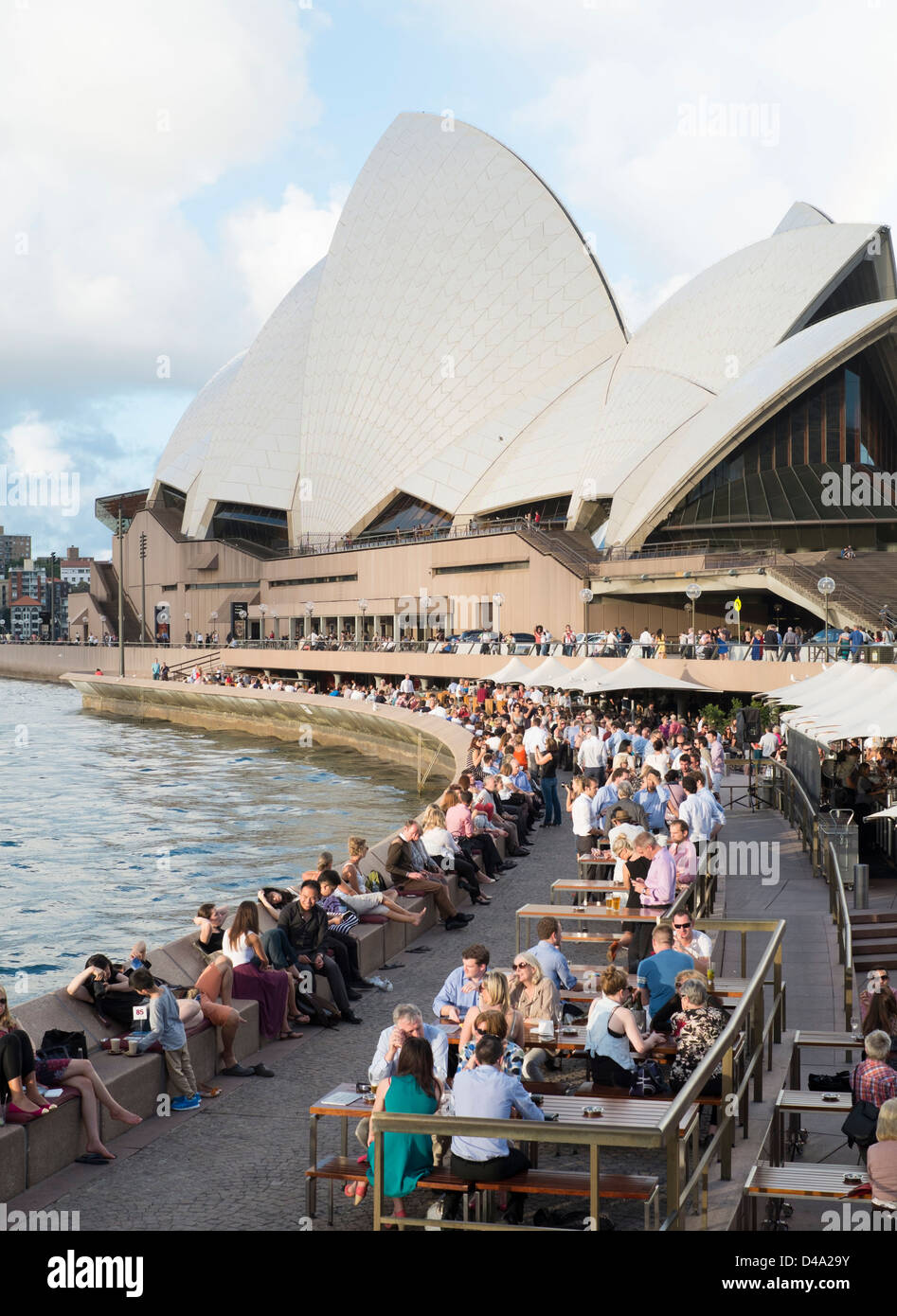 Many people drinking in evening  in bars beside harbour at Sydney Opera House in Australia - Stock Image
