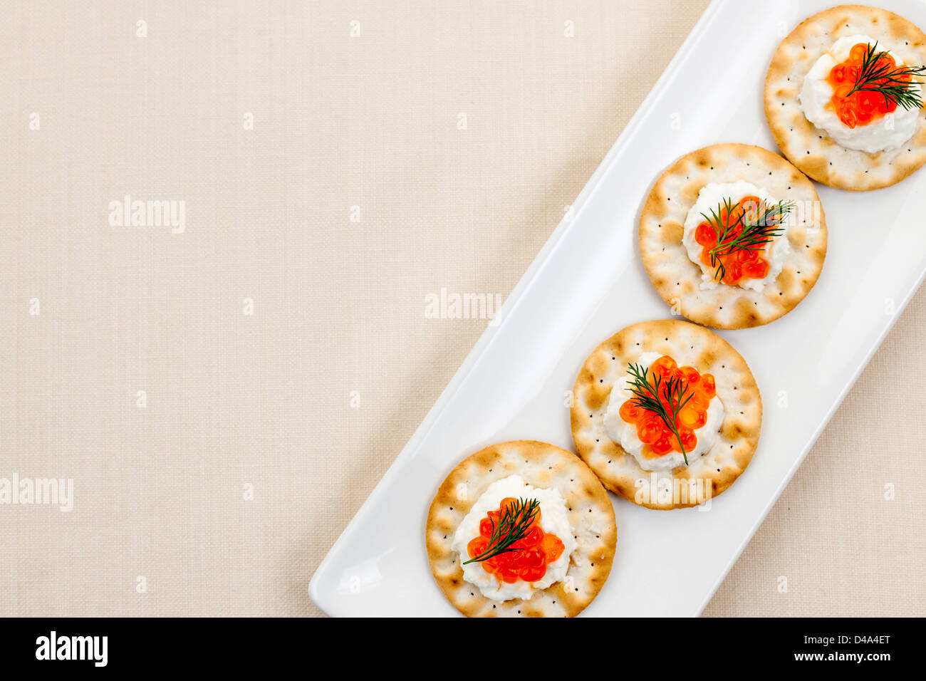 Caviar and goat cheese appetizer on white plate from above with copy space - Stock Image