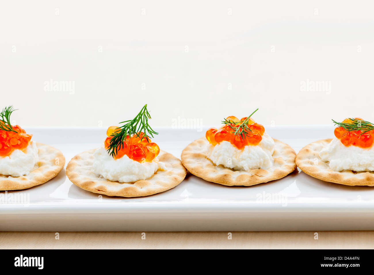 Caviar appetizer with goat cheese and crackers on white plate - Stock Image