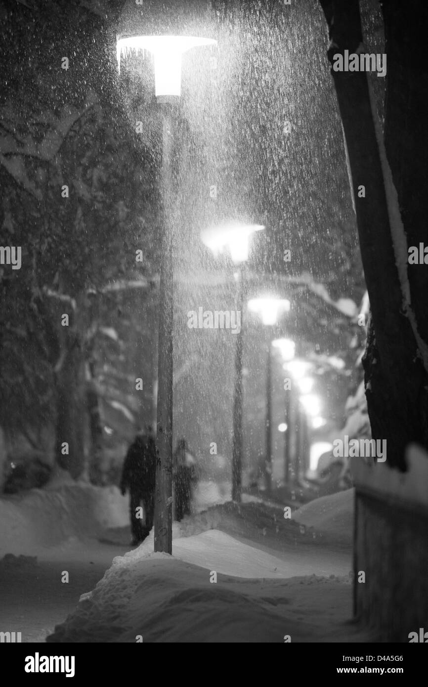 Heavy snow fall on street at night. People are walking under street lights while snowing. Extreme weather. Monochrome - Stock Image