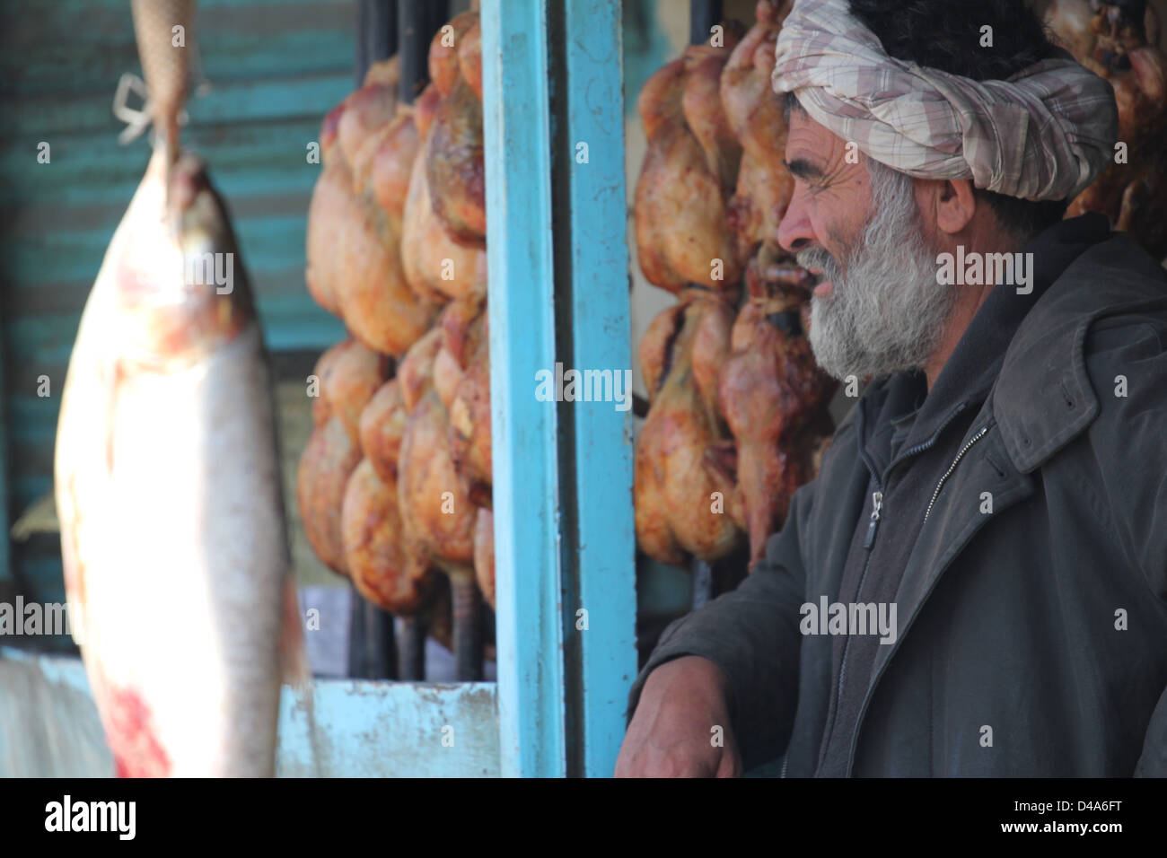 An Afghan male stares onto the street. - Stock Image