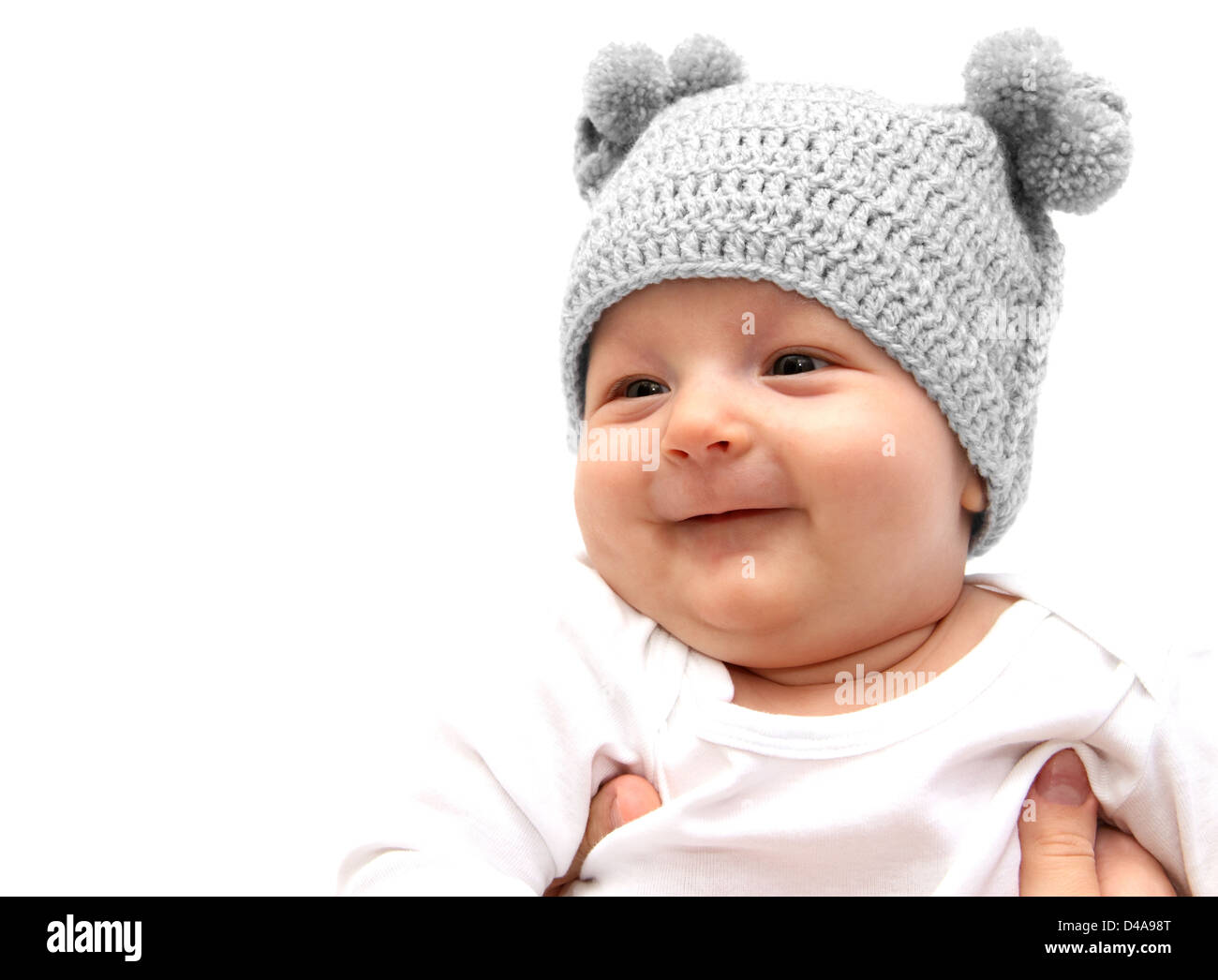 Happy baby in knitted hat in mothers hands - Stock Image