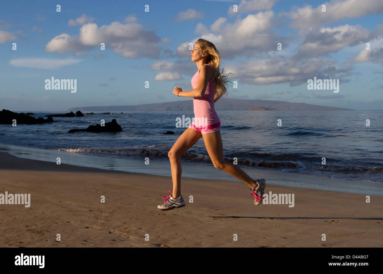 A healthy, fit woman exercises at the beach at Wailea, Maui, Hawaii. - Stock Image