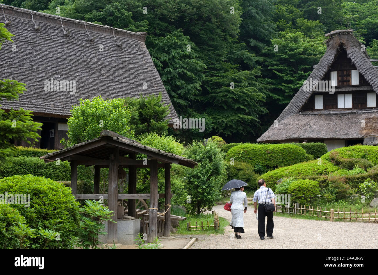 Visitors walking past historic kayabuki thatched-roof village farm houses at the Nihon Minkaen open-air folk museum - Stock Image