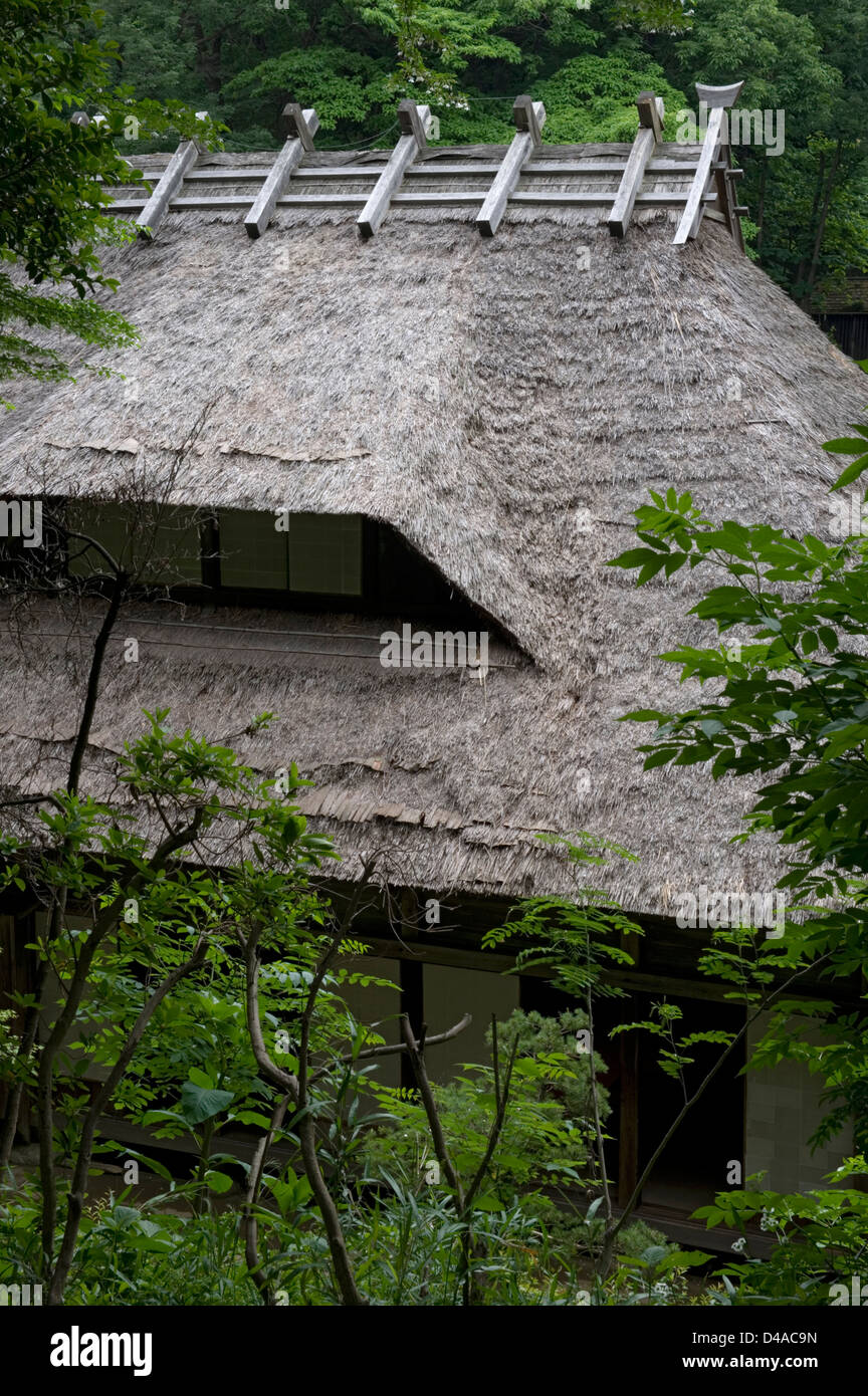 Historic kayabuki thatched-roof village farm houses in forest setting at the Nihon Minkaen open-air folk museum - Stock Image