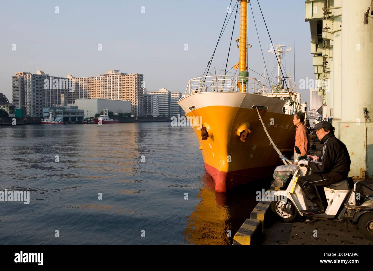 Fishing boat tied up at dock on Tokyo's Sumidagawa (Sumida River) at Tsukiji Wholesale Fish Market, world's - Stock Image
