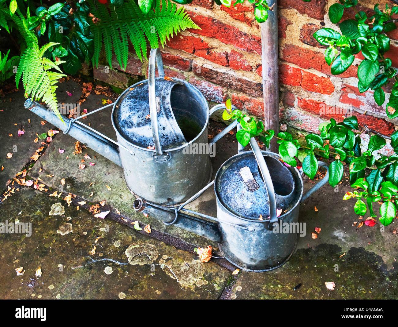 Pair of galvanised metal watering cans - Stock Image