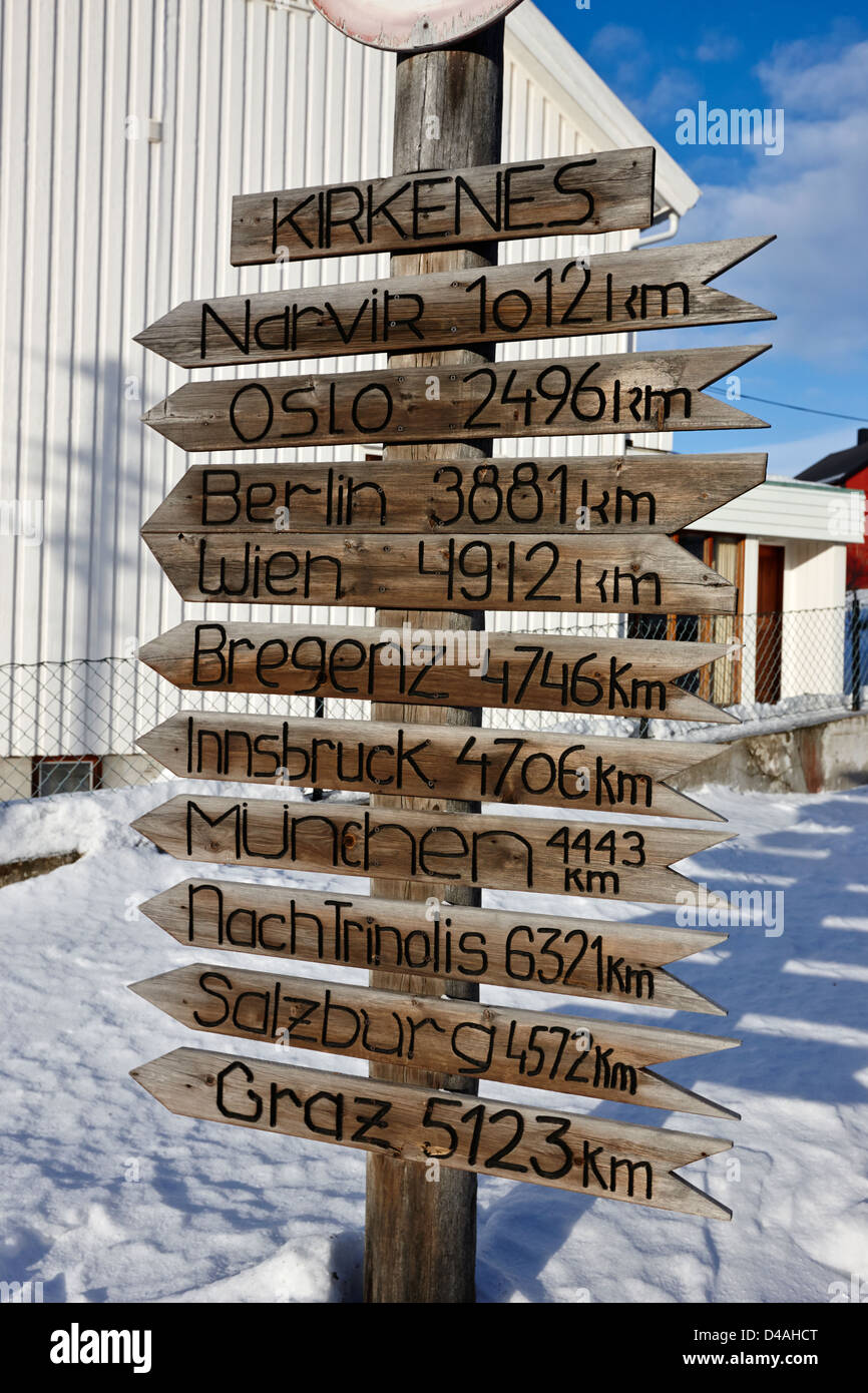 wooden distance marker to various european towns in from kirkenes norway europe - Stock Image