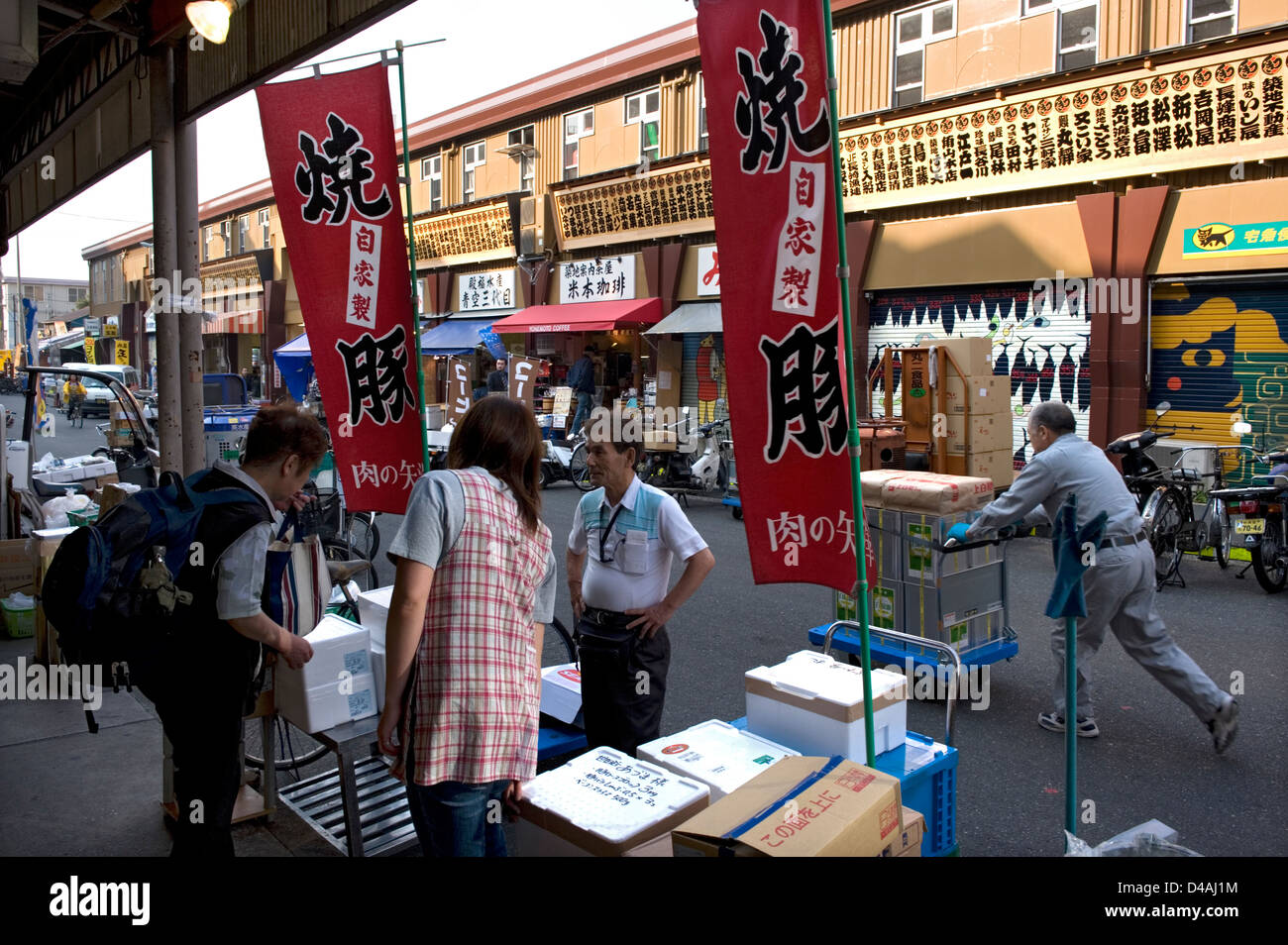 Early morning shoppers looking for fresh seafood and good deals at shops near Tsukiji Wholesale Fish Market in Tokyo. - Stock Image