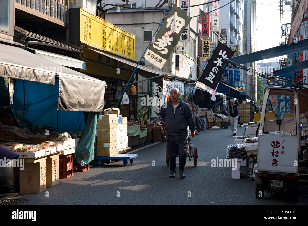 Early morning street lined with shops and restaurants and workers moving about near Tsukiji Wholesale Fish Market - Stock Image