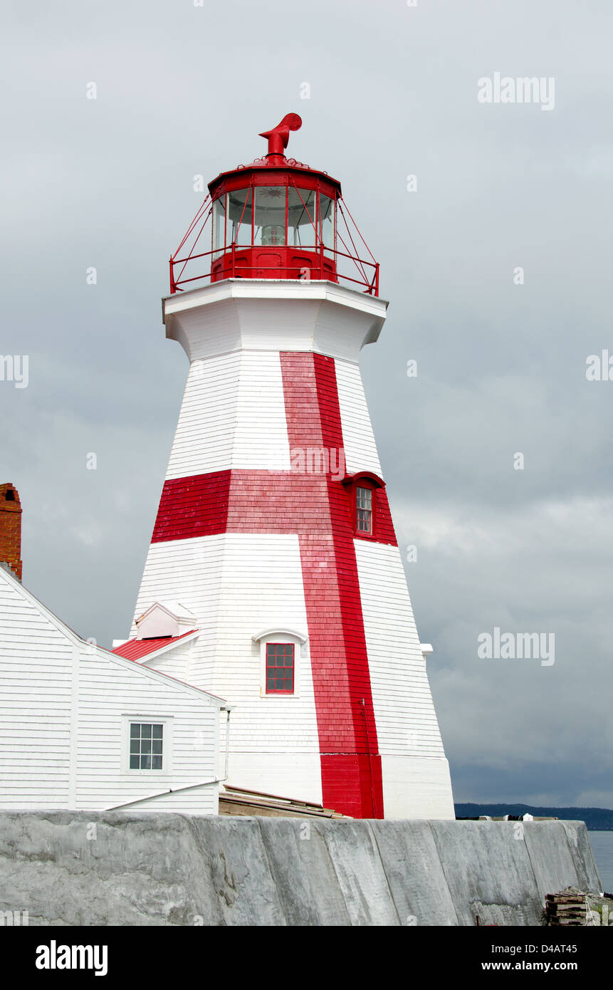 The red and white paint of the East Quoddy Lighthouse gleams in a ray of sun against a stormy gray sky. - Stock Image