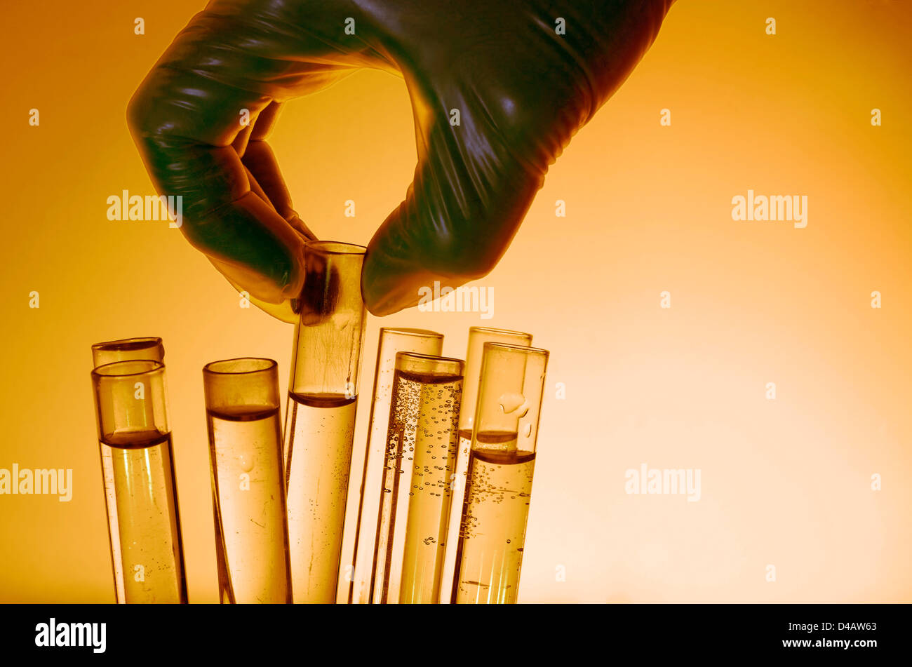 Researcher's hand silhouetted in laboratory - Stock Image