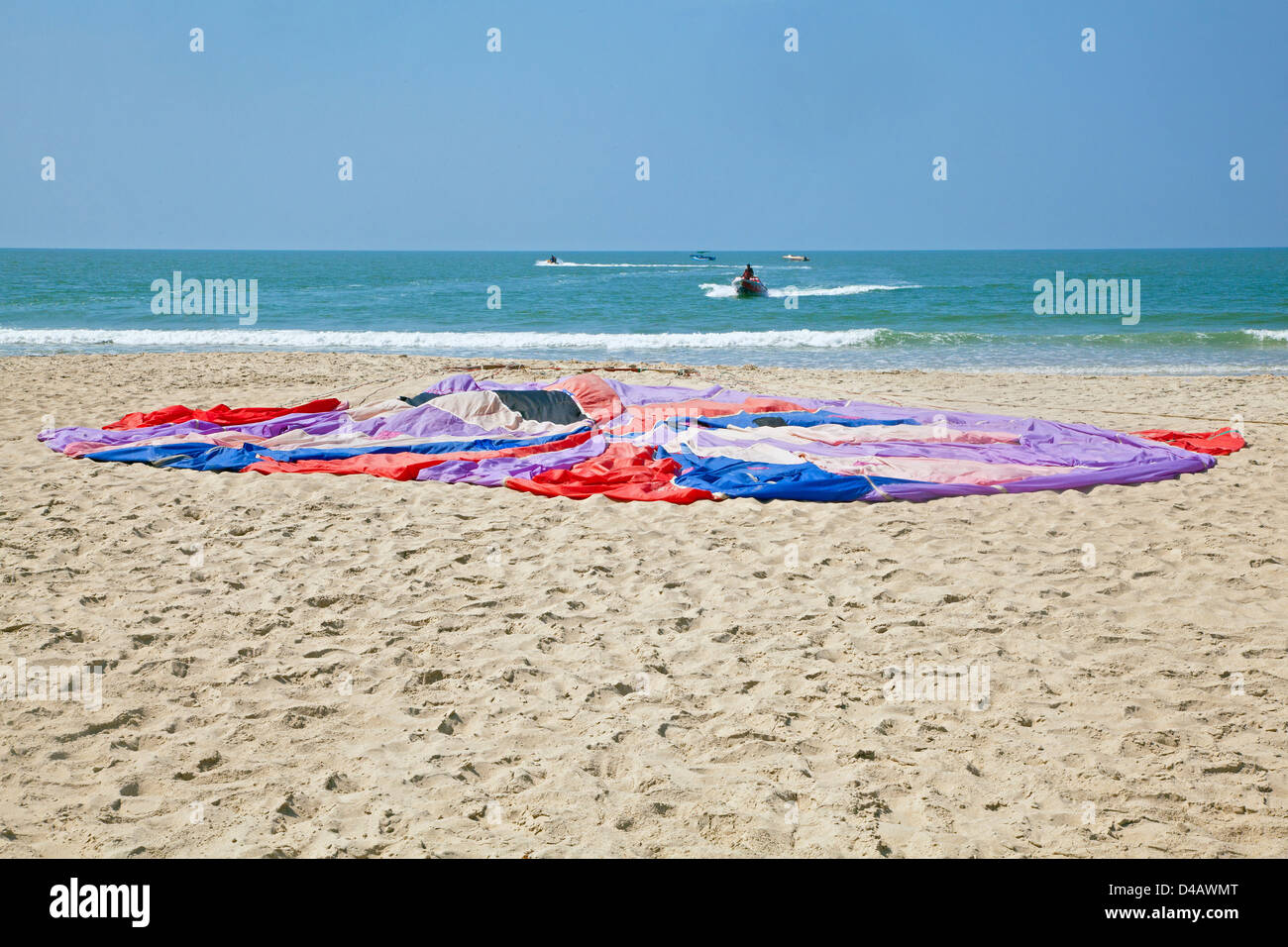 Generic beach landscape of seaside activity and sports of parachute laid flat on beach to dry in hot indian sun Stock Photo