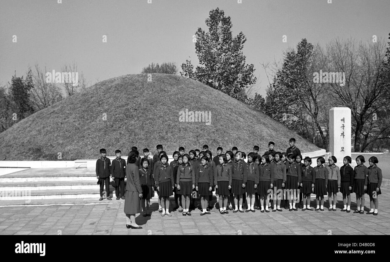 North Korean pioneers stand in front of a mass grave hil in the Sinchon museum concerning US war crimes, photographed - Stock Image