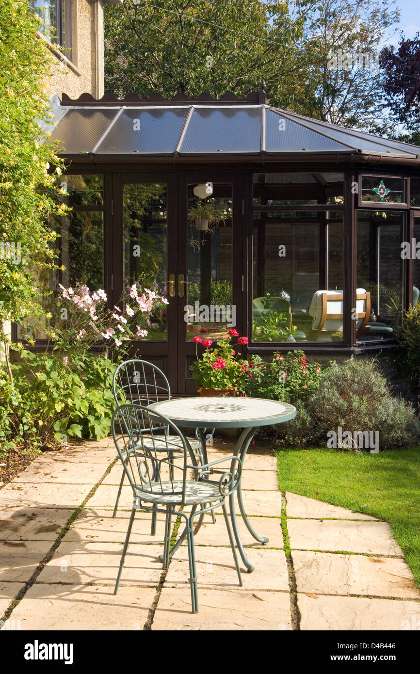 A Small Patio Garden Table And Chairs Outside A Conservatory.