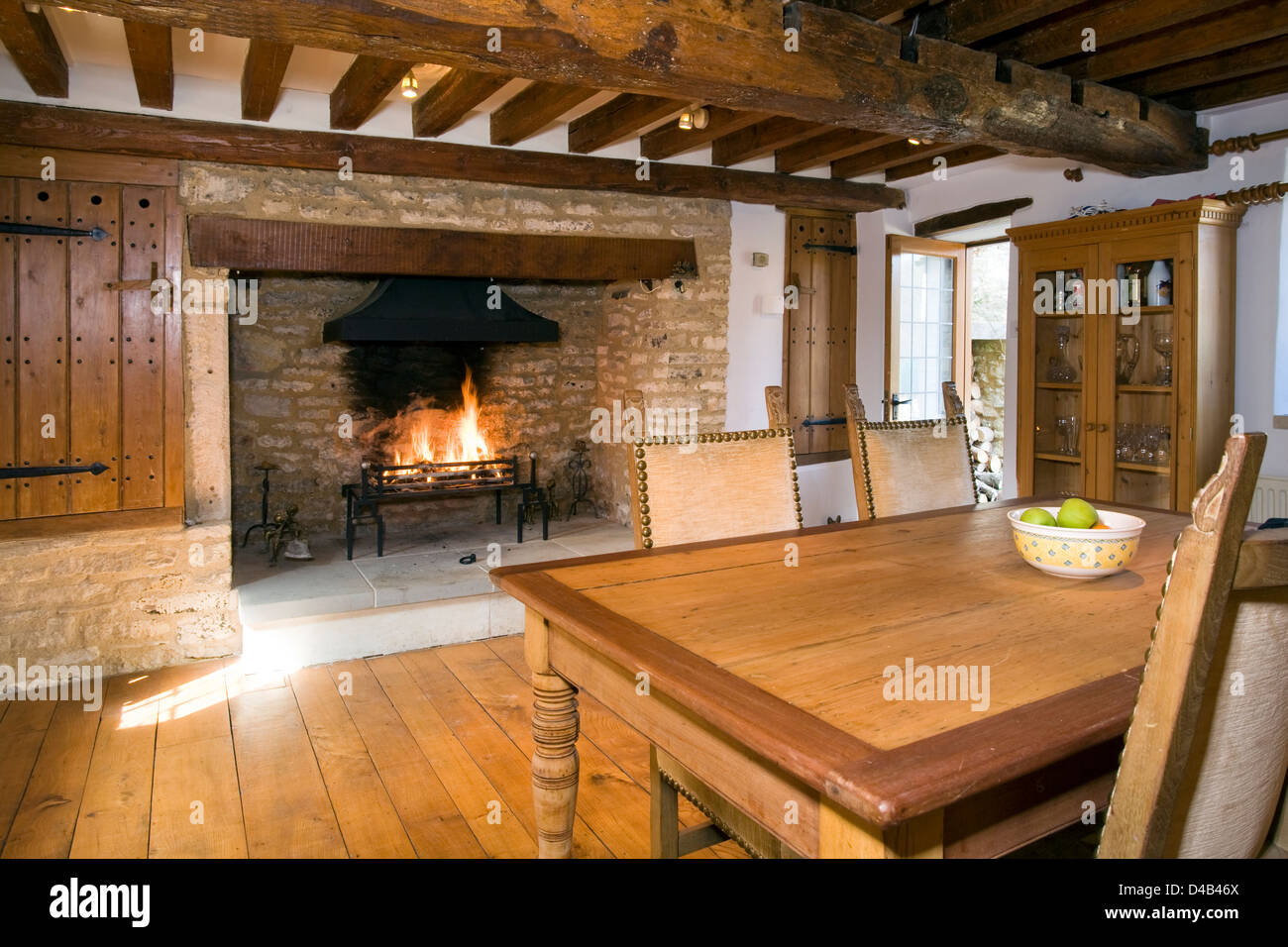 An arts and crafts style cottage dining room with a large fireplace. - Stock Image