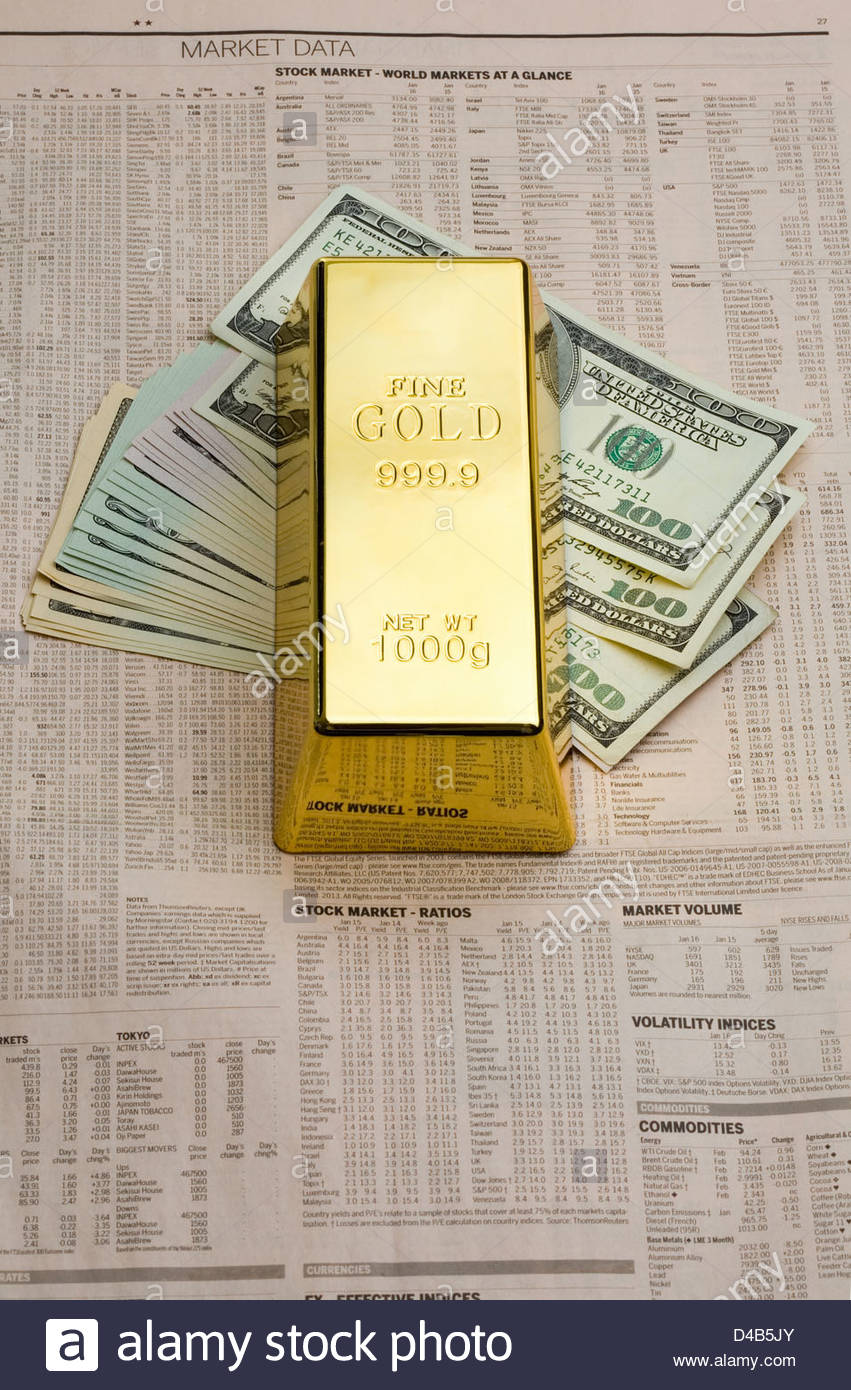 Gold ingot paper weight laying on dollar bills on the financial pages of a newspaper. - Stock Image