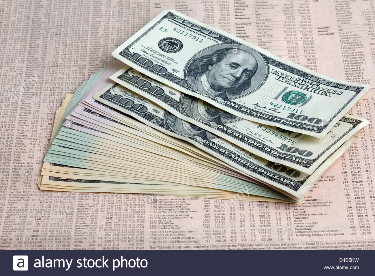 Dollar symbol laying on dollar bills on the financial pages of a newspaper. - Stock Image