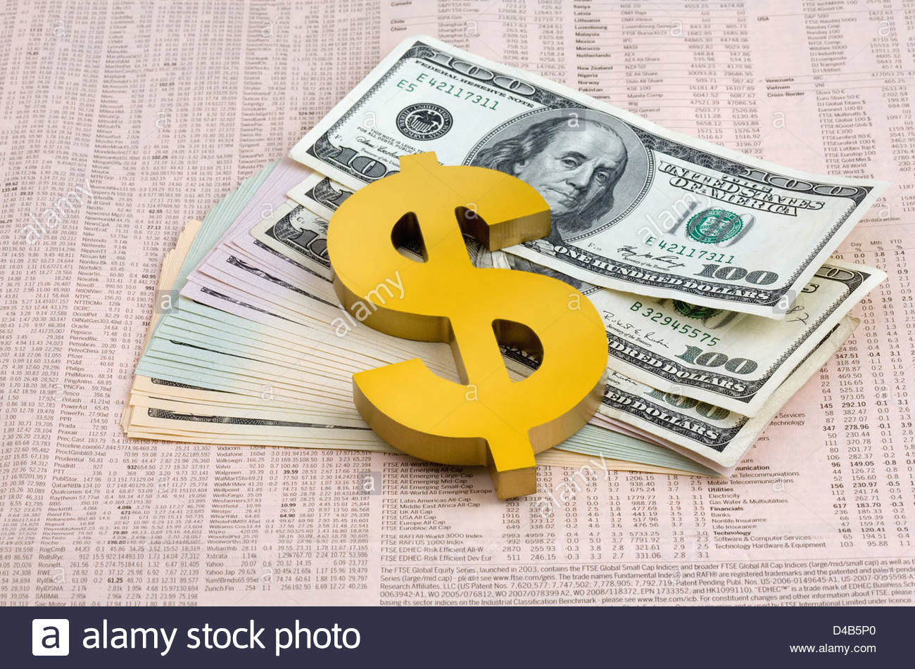 Dollar symbol paper weight laying on dollar bills on the financial pages of a newspaper. - Stock Image