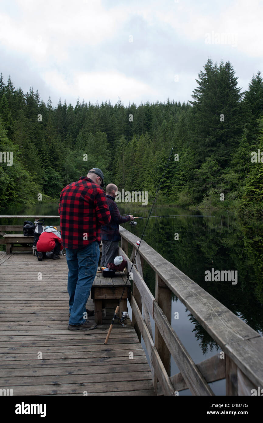 Fishermen fishing off a dock in a freshwater lake in the forest - Stock Image