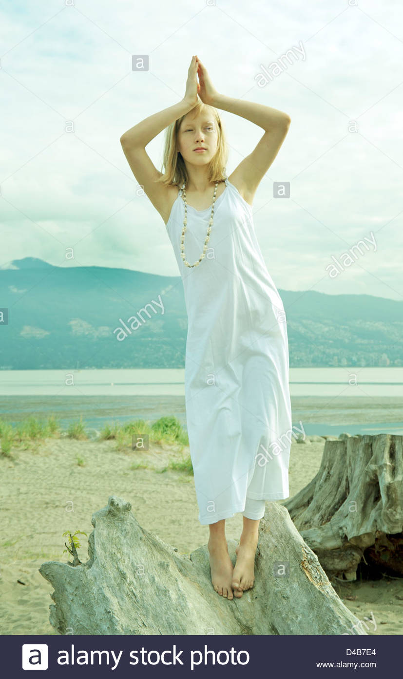 Young girl wearing a white sun dress is standing on log at beach in a yoga pose - Stock Image