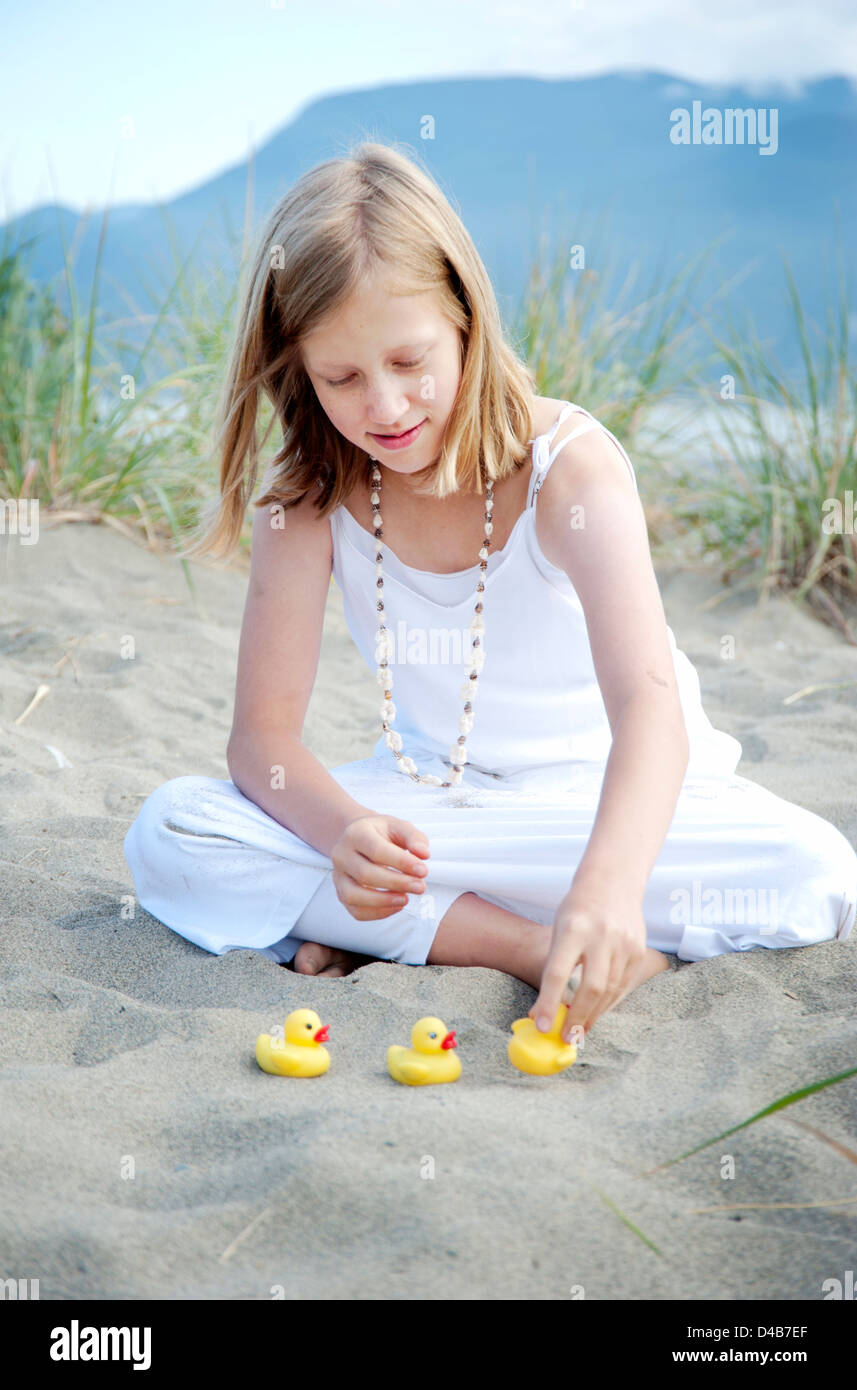 Young girl sitting on beach putting ducks in a row - Stock Image