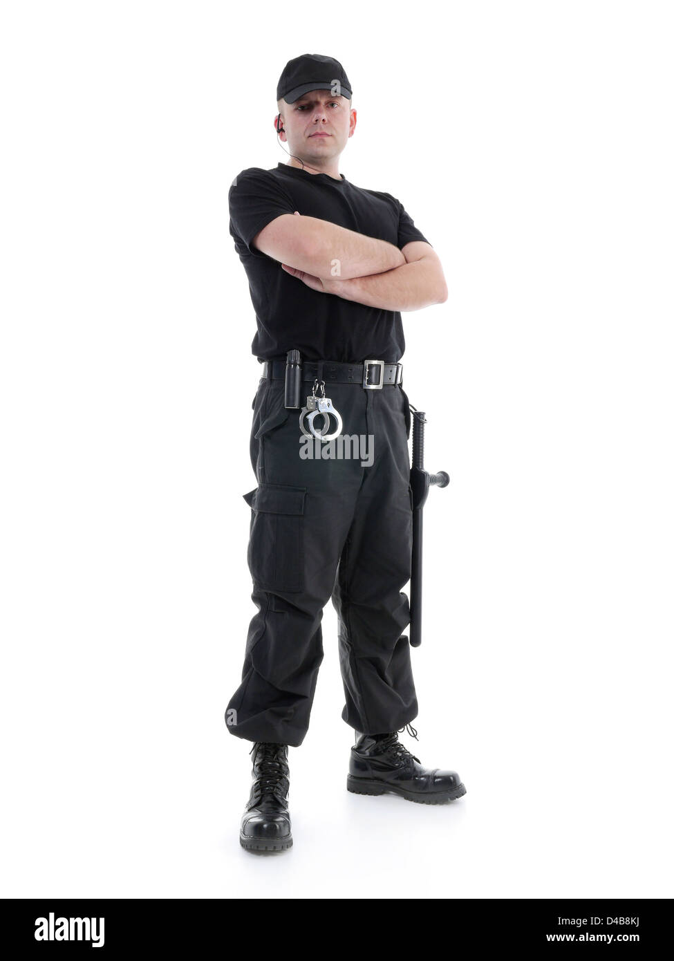 Security man wearing black uniform equipped with police club and handcuffs standing confidently with arms crossed, - Stock Image