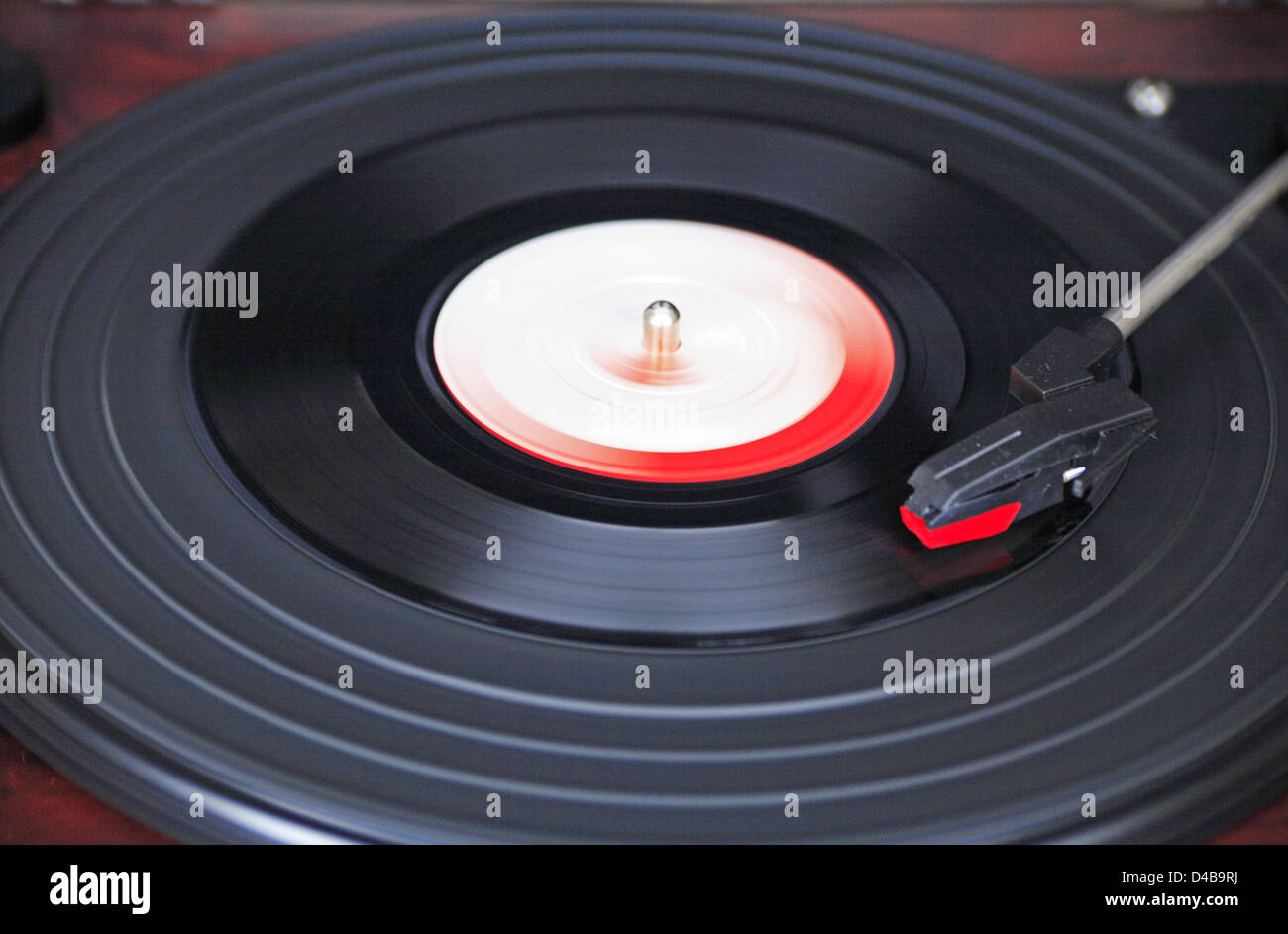 An old vinyl 45 rpm record spinning on a turntable. - Stock Image