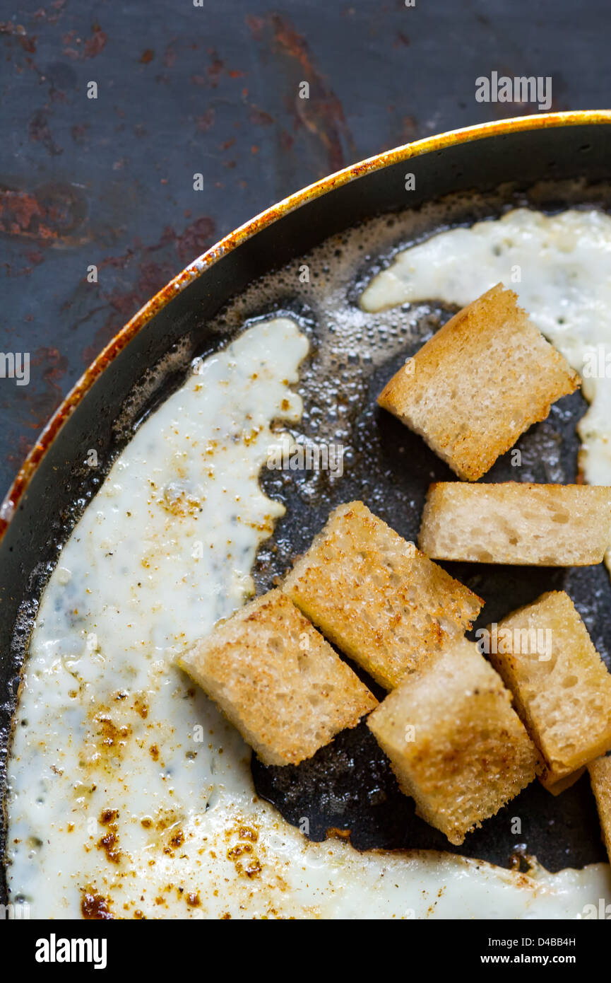 Frying pan full of scramble eggs from two eggs with a small pieces of toasted bread. Stands on grunge metal background. - Stock Image