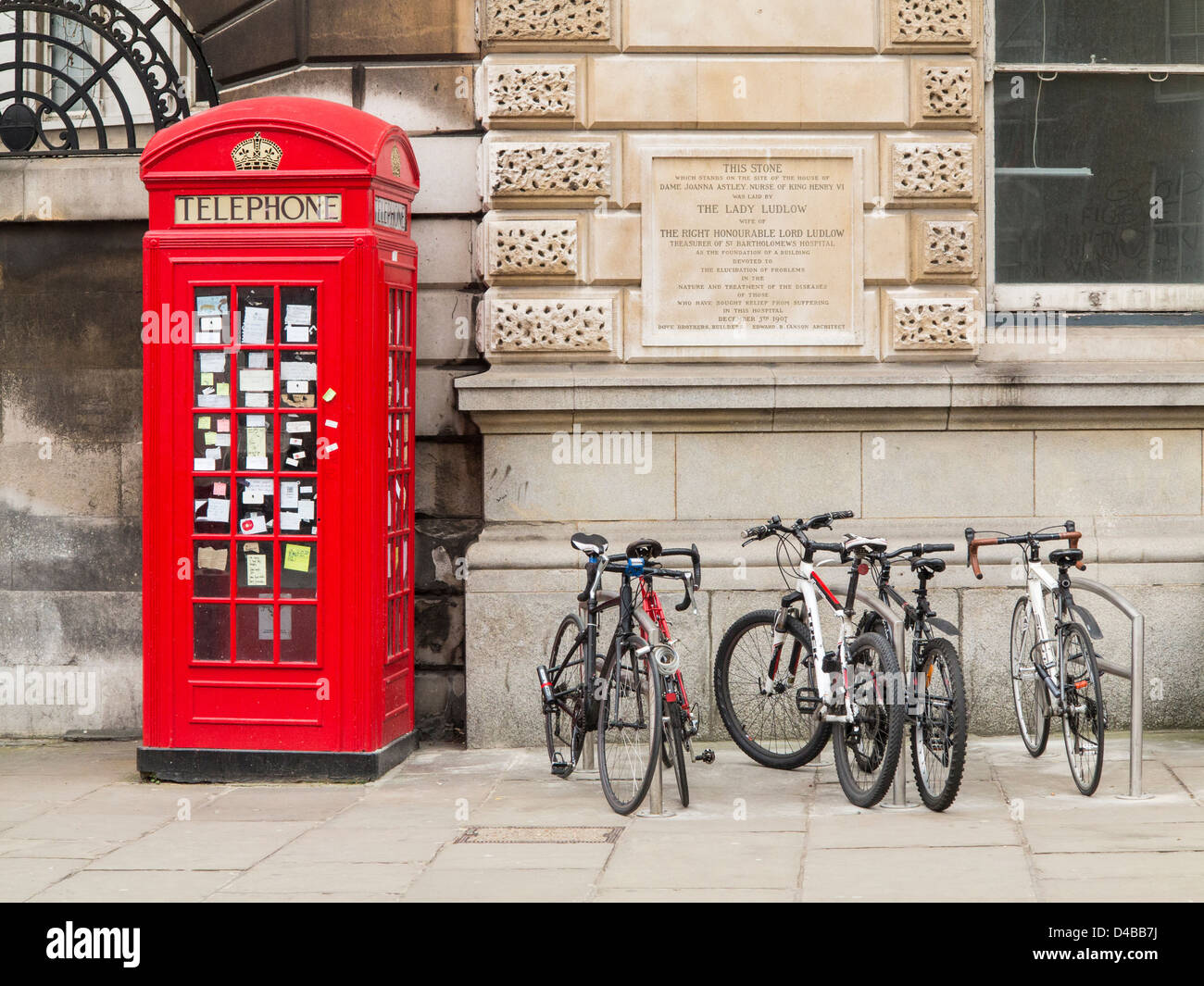 Red old style telephone box and parked bicycles in London, England - Stock Image