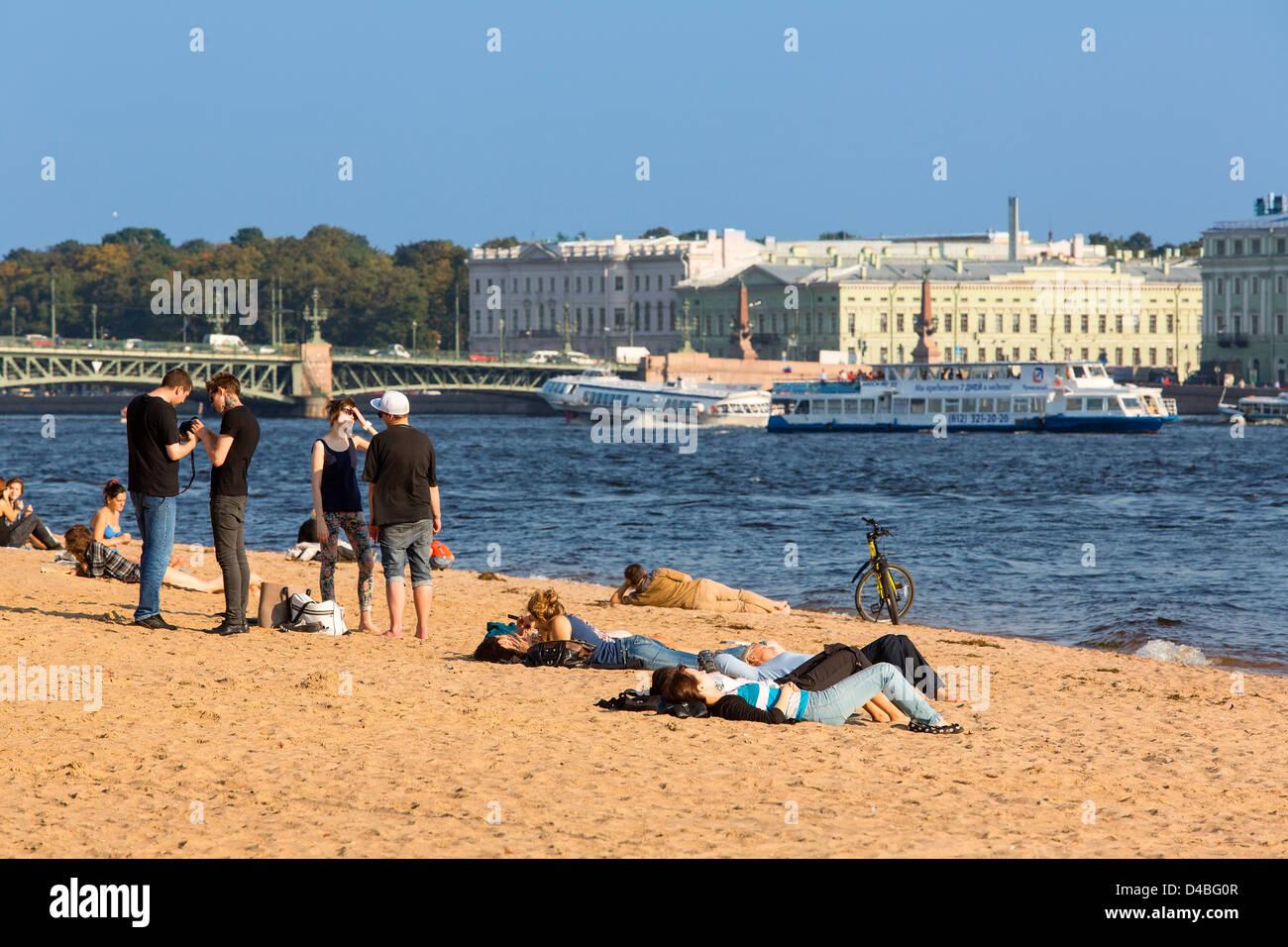 St. Petersburg, People Sunbathing Along the Neva River - Stock Image