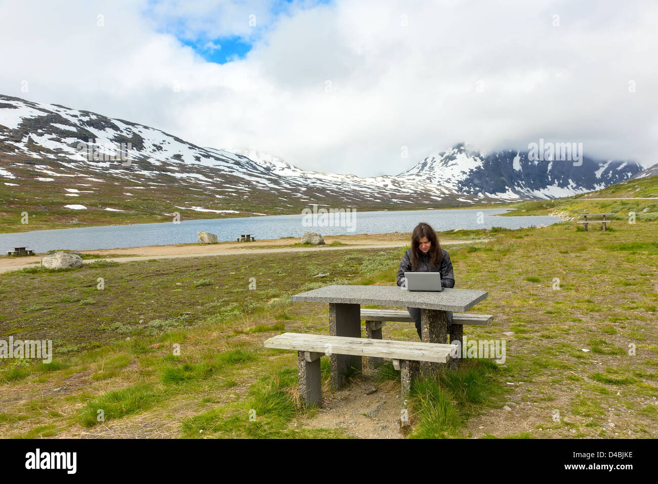 Young girl working on a laptop among mountains, Norway Stock Photo