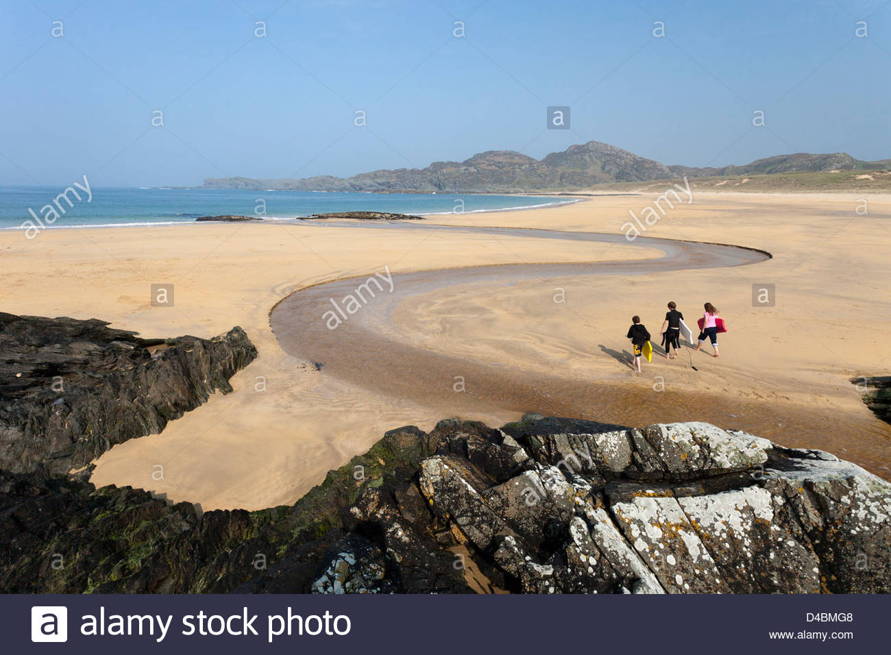 Three children with bodyboards walk across the beach at Kiloran Bay on the Isle of Colonsay, Inner Hebrides, Scotland - Stock Image