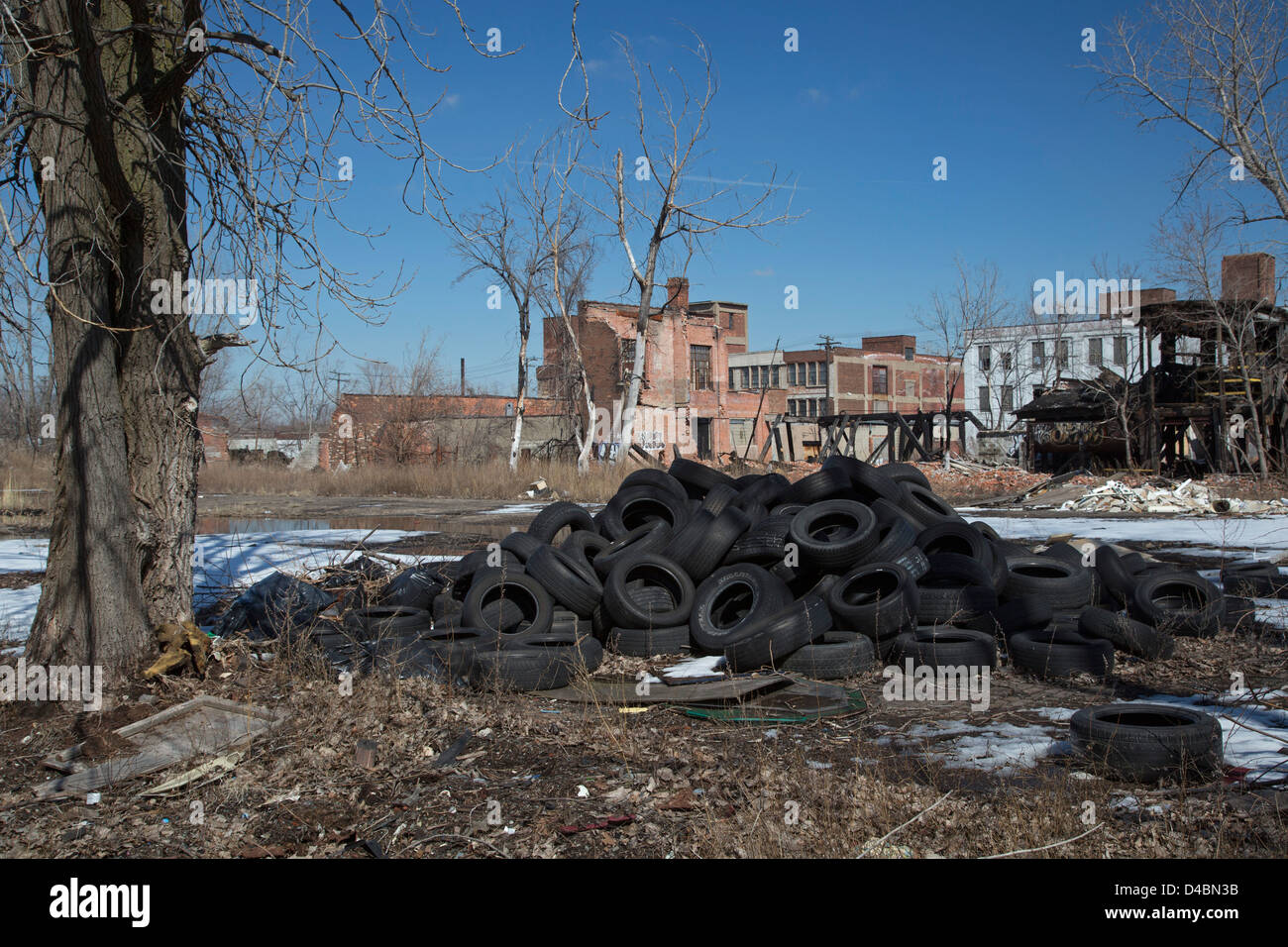 Detroit, Michigan - Used tires dumped on a vacant lot next to derelict buildings. - Stock Image