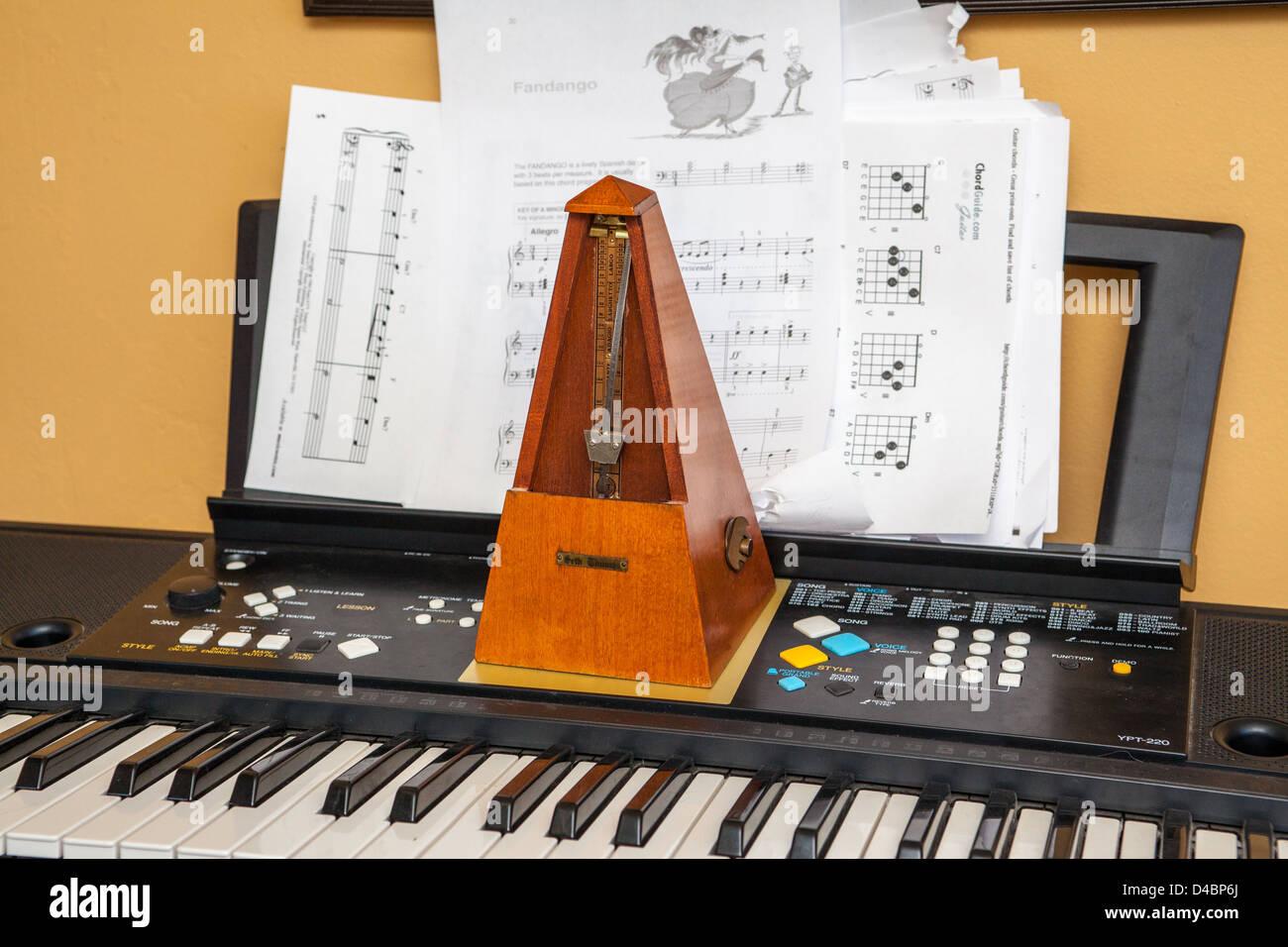 A metronome sheet music and electronic keyboard - Stock Image