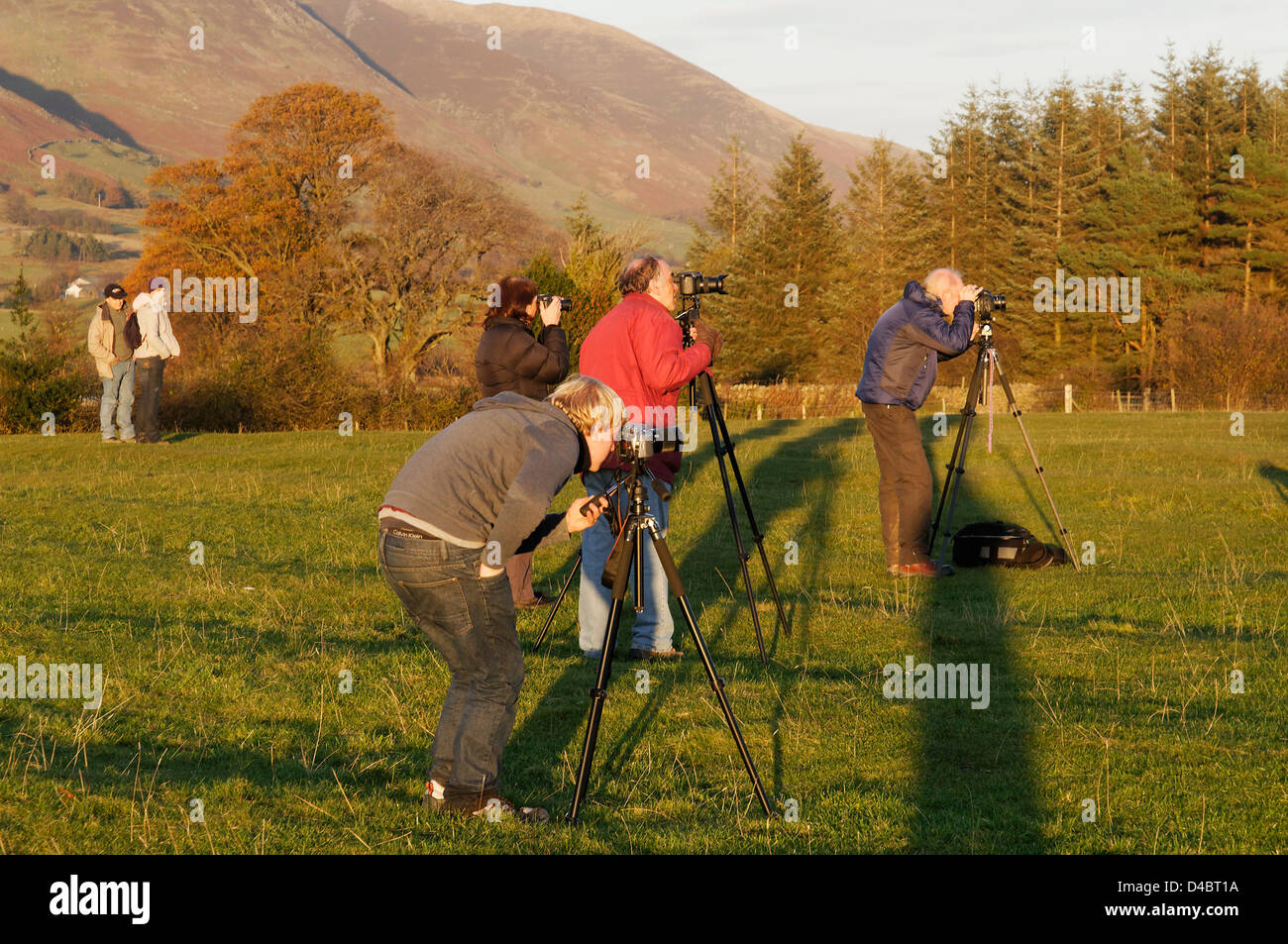 Photographers with their tripods lined up ready for sunset - Stock Image