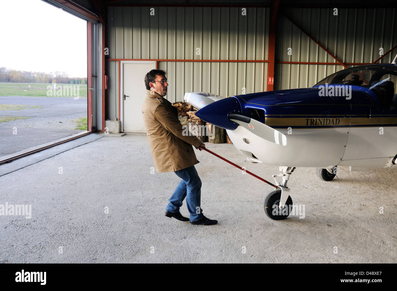 A pilot pulling his light plane out of its hangar Stock Photo