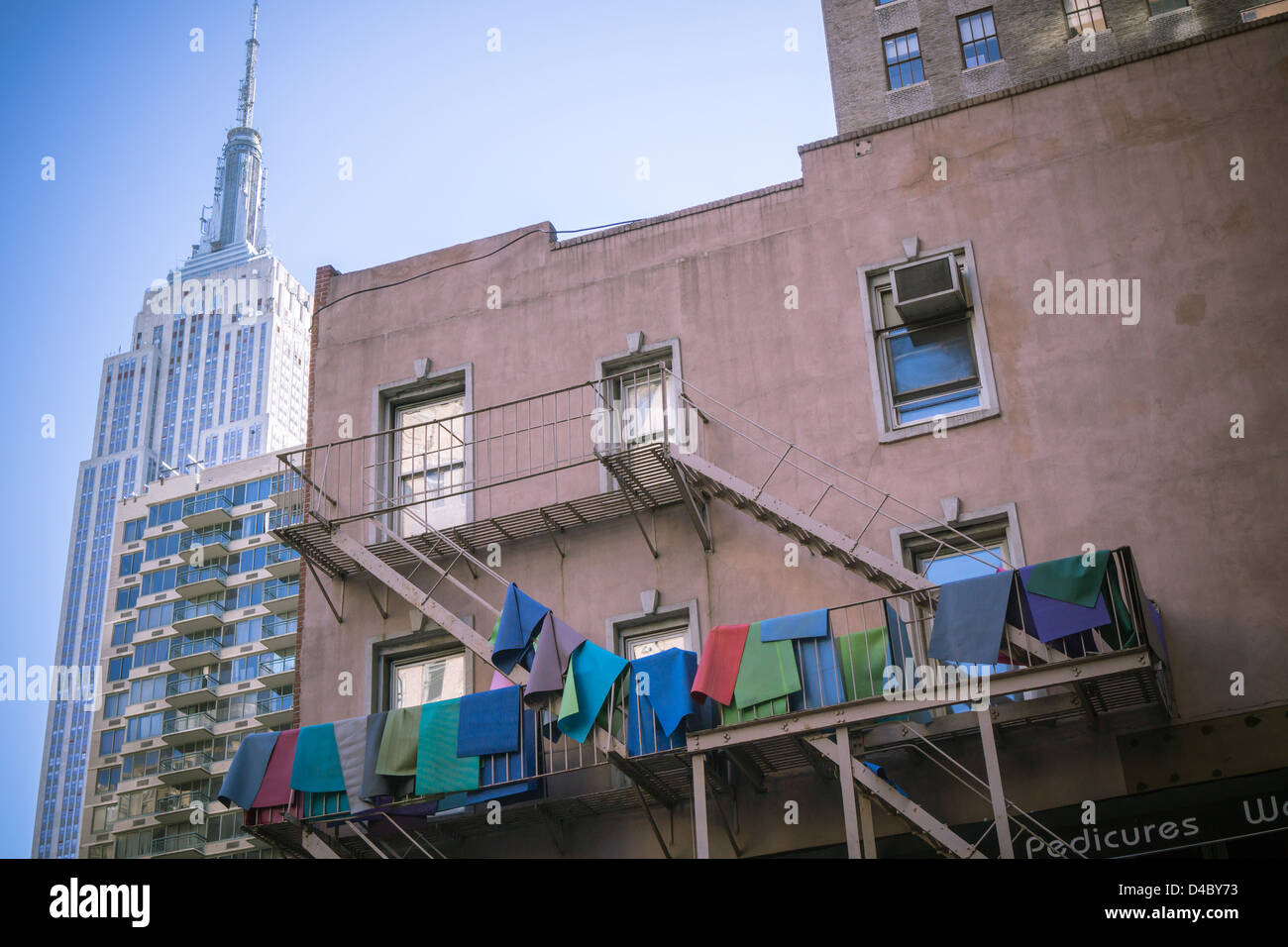 A yoga studio in Midtown Manhattan in New York airs out their yoga mats on a fire escape - Stock Image