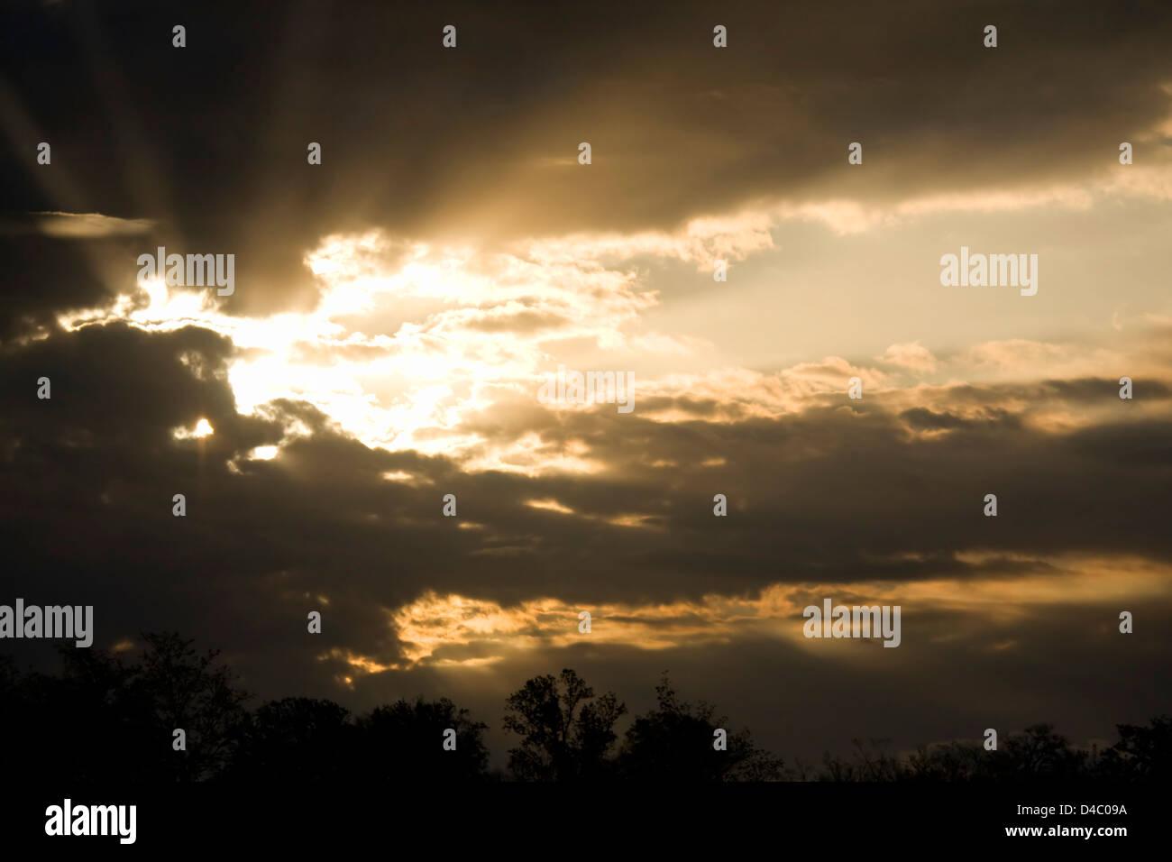 Rays of sun bursting through storm clouds. Stock Photo
