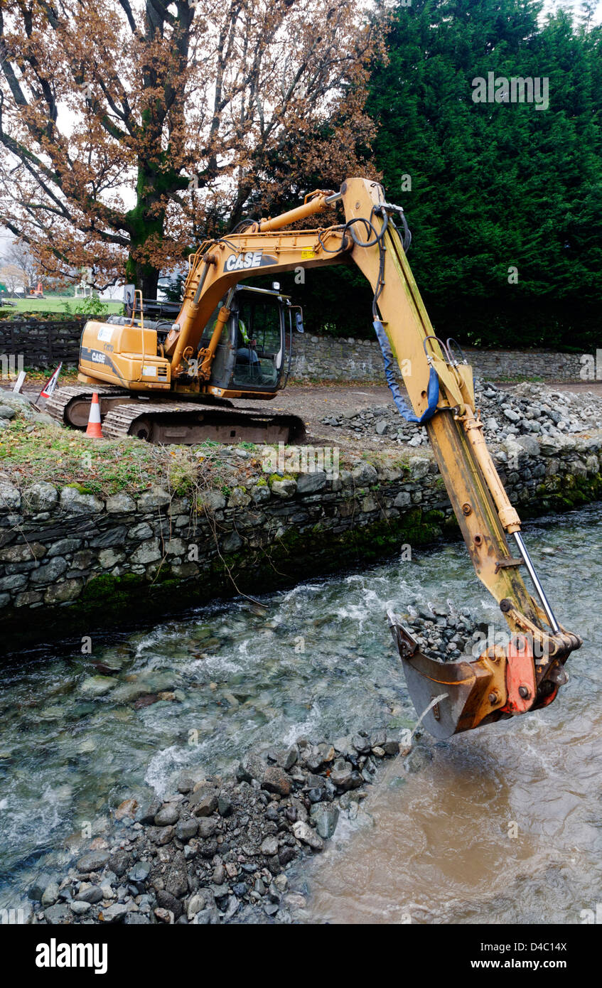 A JCB type digger working in a river in Patterdale, The Lake District, England - Stock Image