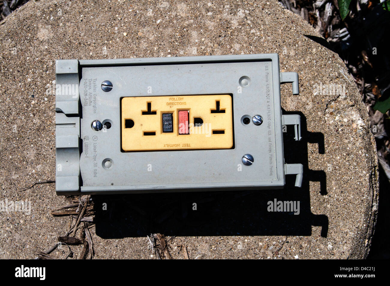 Ground fault GFCI electric receptacle sitting on a cement platform. Chicago Illinois IL USA - Stock Image