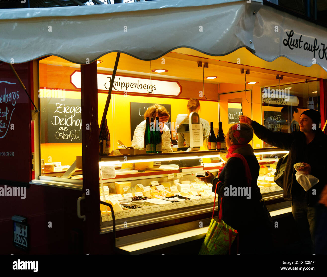 People buying cheese in Markthalle 9 indoor market, Berlin - Stock Image