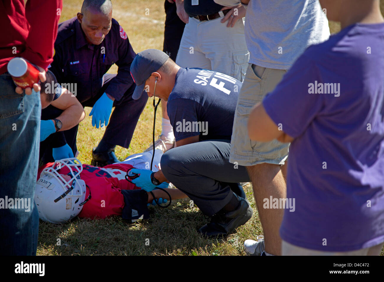 Paramedic checking blood pressure of injured football player with possible concussion. Conway Park St Paul Minnesota - Stock Image