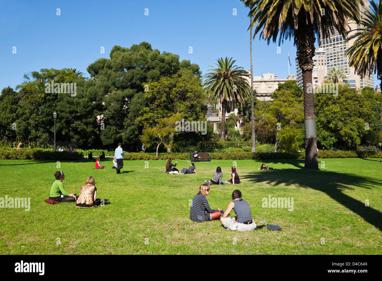 City workers relaxing on the lawn at Carlton Gardens. Fitzroy, Melbourne, Victoria, Australia - Stock Image