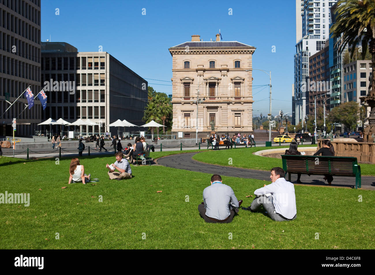 City workers relaxing on the lawn at Parliament Gardens. Fitzroy, Melbourne, Victoria, Australia Stock Photo