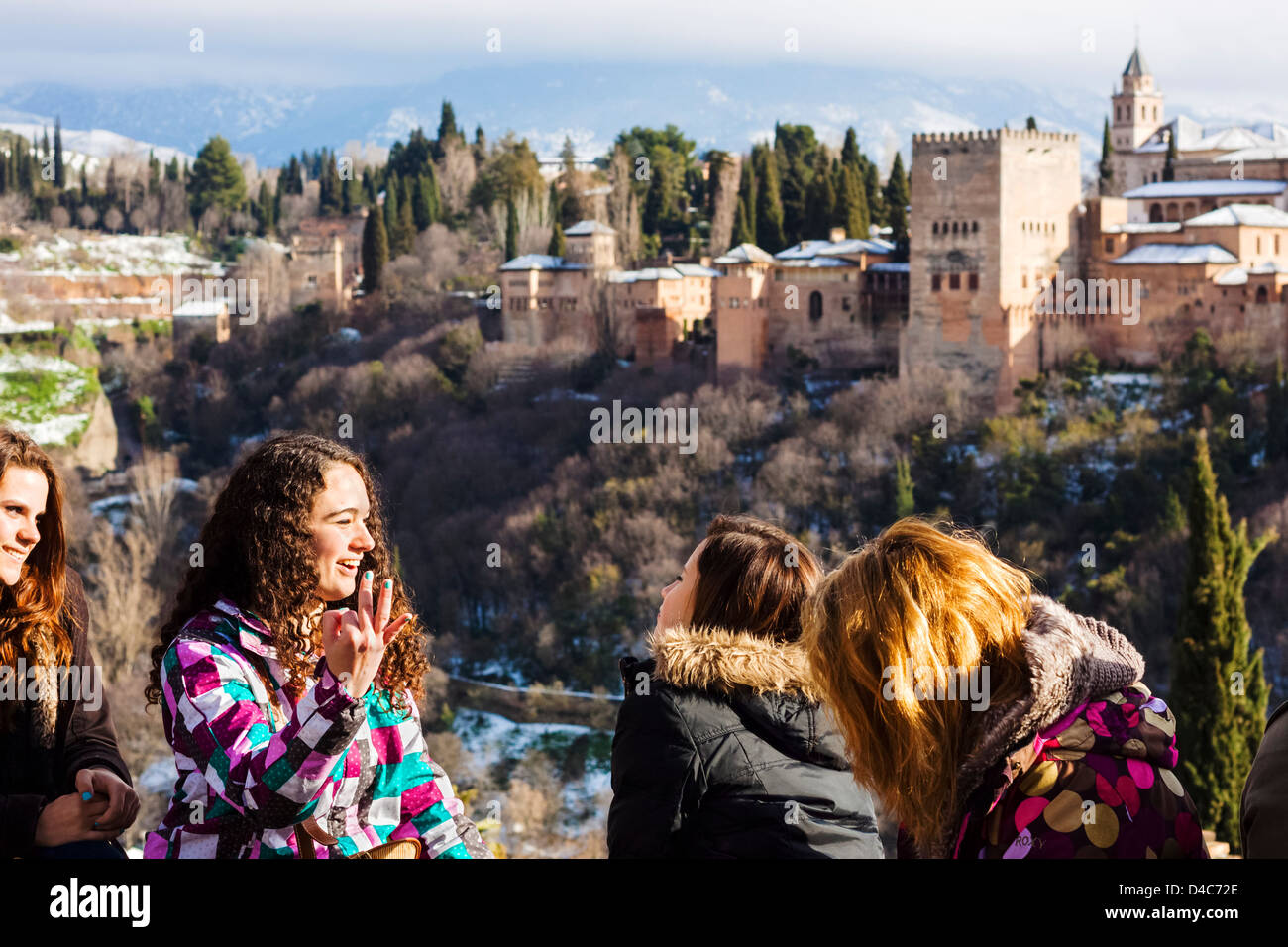 Cheerful teenager female tourists with snowy Alhambra palace in background. Granada, Spain - Stock Image